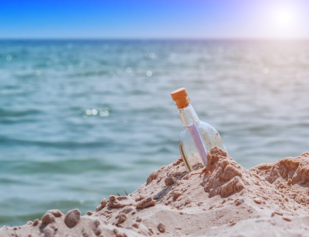 bottle with a note on the beach near the water under sunlight