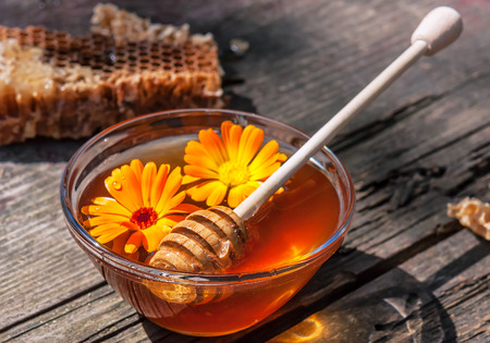 conformity: fresh sweet honey with stick and calendula flowers n glass bowl Stock Photo
