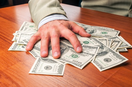 businessman in business suit takes dollars Stock Photo