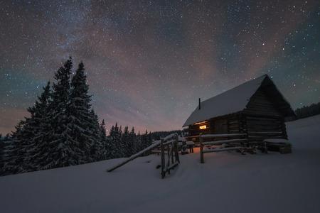 별이 빛나는 하늘 겨울 풍경입니다. 산속 오두막의 등불