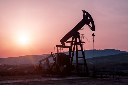 silhouette of oil pump on beautiful red sunset Stock Photo