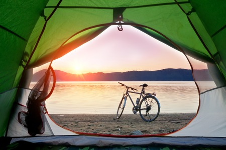 view from the tent to the lake with bicycle on sunset
