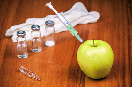 vaccine syringe and juicy apple. Genetic modification theme