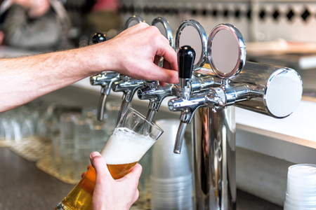 beer taps and goblet with fresh tasty beer Stock Photo