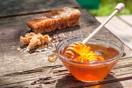 conformity: fresh honey in glass bowl on old wooden table Stock Photo