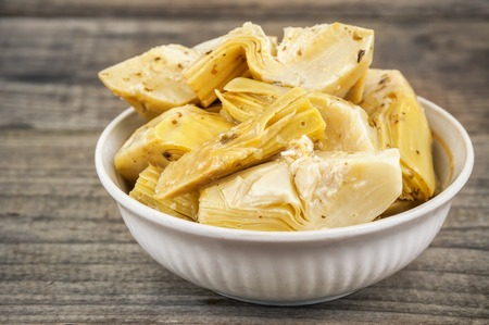 marinated delicious artichokes in bowl on wooden background Stock Photo