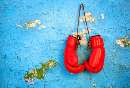 red boxing gloves on blue cracked wall