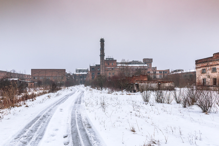 Ruins of abandoned factory in winter. Dramatic sky