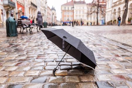 black opened umbrella on the wet pavement