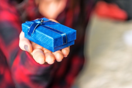 blue gift box in womans hand