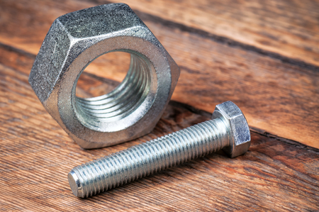 silver bolt and nut on wooden background