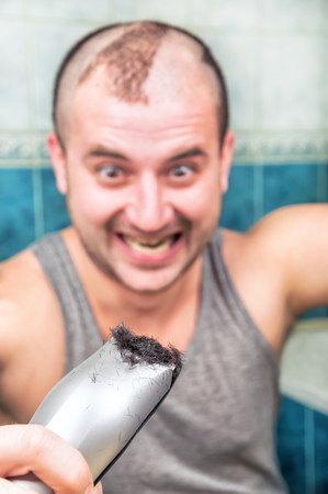 crazy man cuts himself by the hair clipper Stock Photo