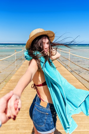 Traveling together. Follow me. Young woman in straw hat holding boyfriends hand walking on the pier