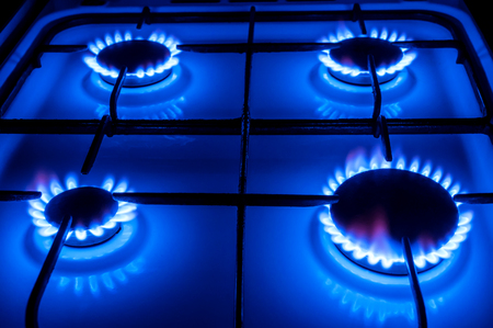 four gas burners with blue flame