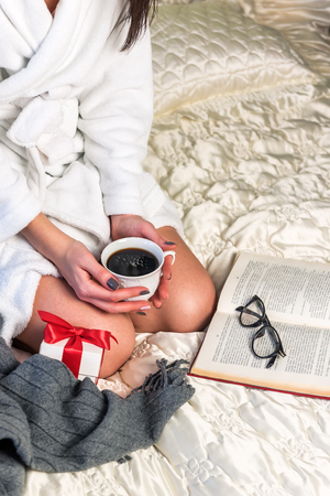 girl with cup of coffee, white gift box with red ribbon and book on the bed