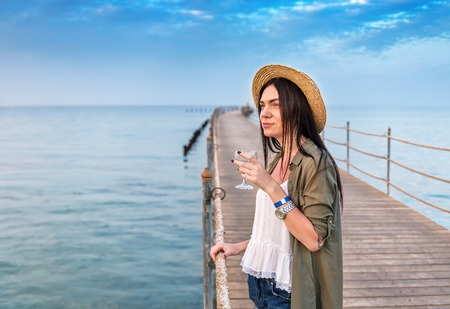 girl in straw hat with glass of wine on the wooden pier on sunset