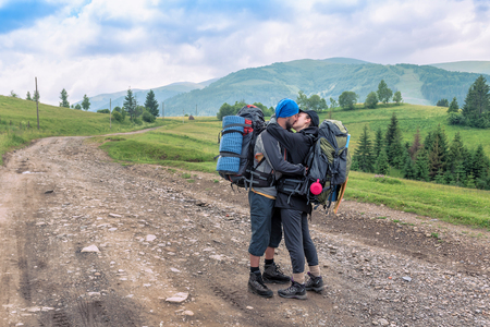 happy kissing couple with backpacks on the road in the mountain Stock Photo