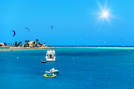 kite sportsman and yacht in the sea under blue sky