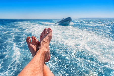 Relaxing man (legs) on the yacht in sea. Stock Photo