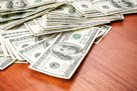 heap of money (dollars) on the table as wallpaper Stock Photo
