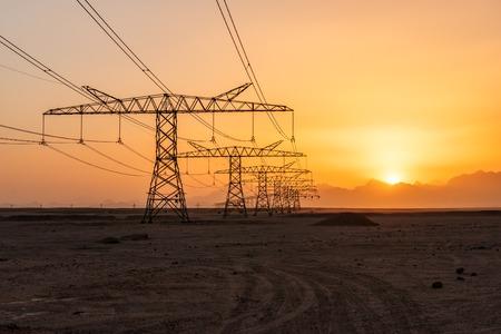 Hochspannungsstromturm und Stromleitungen in der Wüste bei schönem Sonnenuntergang