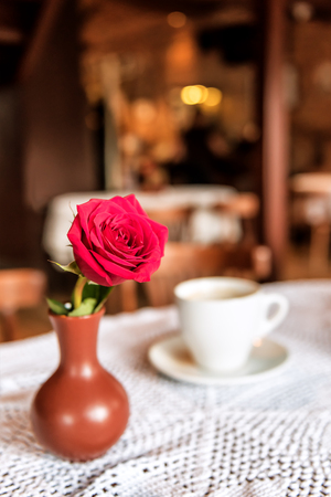 red rose and cup of coffee on white napkin