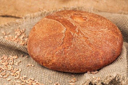 delicious loaf of round fresh bread on burlap napkin Stock Photo