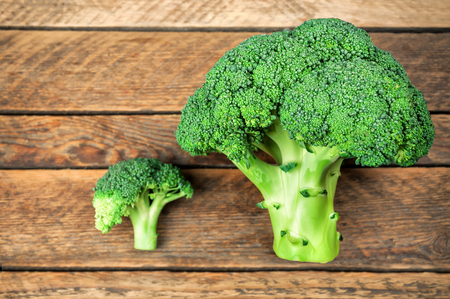 two fresh raw broccoli on wooden background