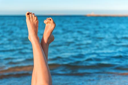 Vrouwelijke benen met kleur pedicure op de achtergrond van de zee Stockfoto