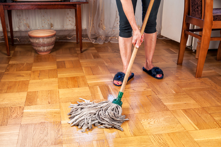 woman cleaning parquet floor with mop