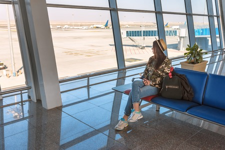 young girl with backpack in airport terminal waiting for flight