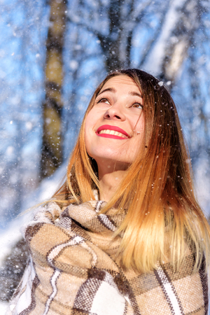 portrait of smiling beautiful girl under snowing