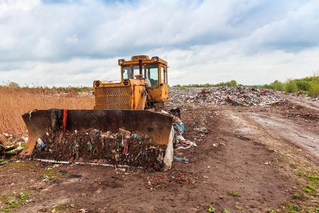 yellow bulldozer in a garbage dump