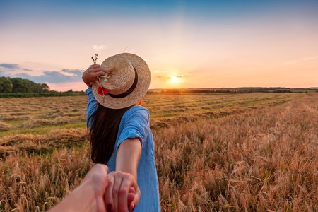 Traveling together. Follow me. Young woman in straw hat holding boyfriend's hand walking in the field on sunset 스톡 콘텐츠