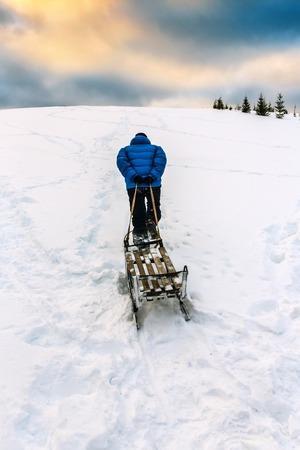 ski walking: A man walking with sled up to the hill at ski resort