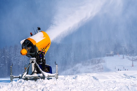 professional artificial snow machine cannon making snowflakes from water at ski resort
