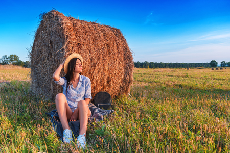 young beautiful girl under straw bale
