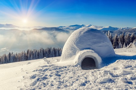 real snow igloo in the mountains under blue sky and sun Stock Photo
