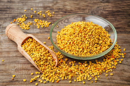 raw organic bee pollen over wooden board