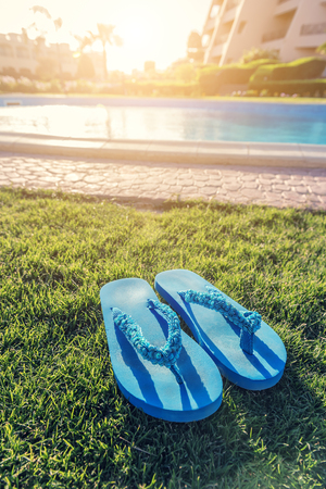 blue flip flop sandals on the grass near the pool