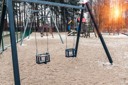 two empty children swings on playground Stock Photo