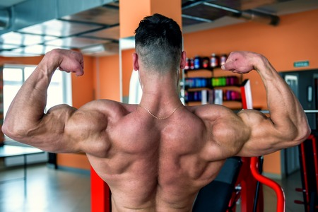 bodybuilder shows his muscular back in the gym