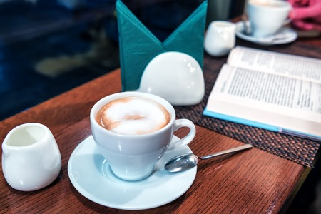 delicious coffee with milk and opened book Stock Photo