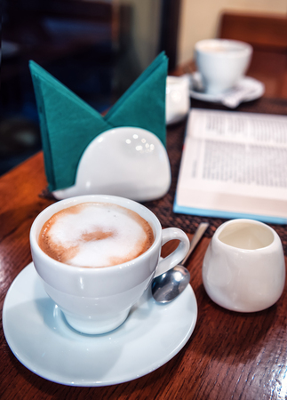delicious coffee with milk and opened book in the cafe Stock Photo