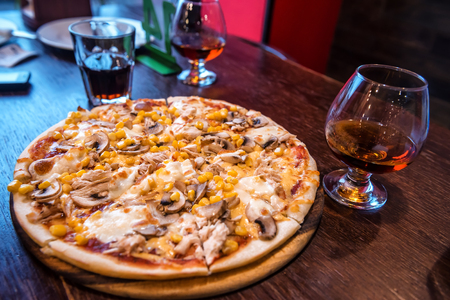 delicious pizza with corn, mushrooms, cheese and glass of brandy Stock Photo