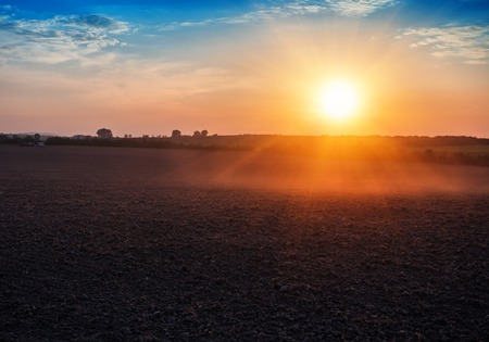 landscape of plowed field on beautiful sunset