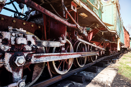 iron wheels of stream engine locomotive train on railways track perspective to golden light forward use for old and classic period land transport and retro vintage style background