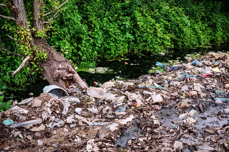 Small river full of different garbage. Environment polution problem Stock Photo