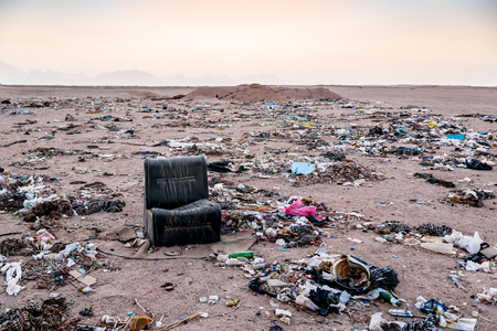 black chair and different garbage in desert
