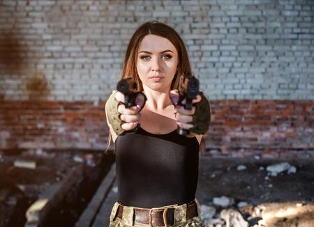 Linda chica militar con dos pistolas en edificio abandonado